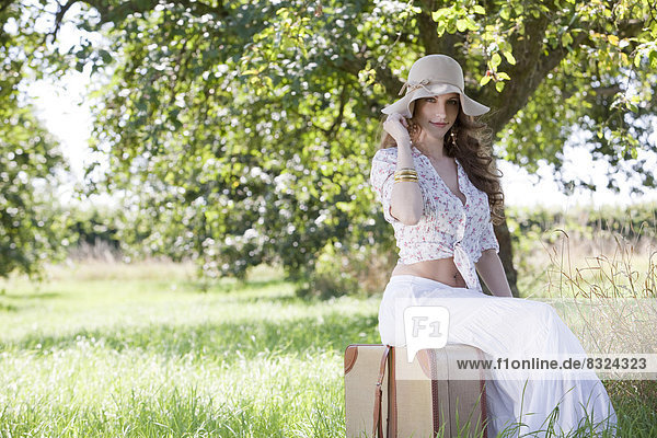 Brunette young woman with suitcase on field