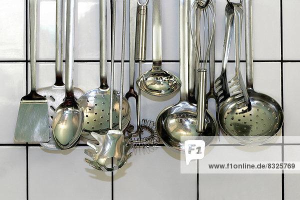 Diverse Küchenkellen vor einer weißen Kachelwand