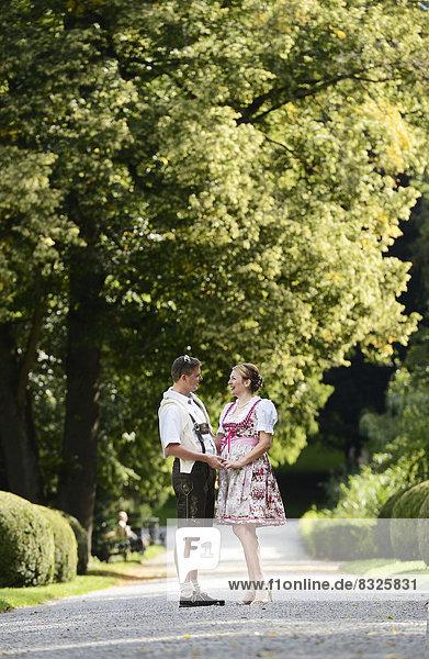 Mann in Lederhose und Frau in Dirndl im Schlosspark Ambras Mann in Lederhose und Frau in Dirndl im Schlosspark Ambras