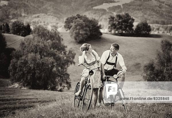 Mann in Lederhose und Frau in Dirndl auf alten Fahrrädern in der Natur Mann in Lederhose und Frau in Dirndl auf alten Fahrrädern in der Natur