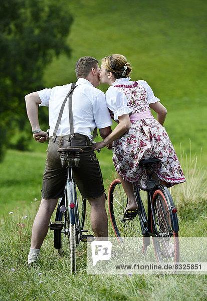 Mann in Lederhose und Frau in Dirndl küssen sich auf alten Fahrrädern in der Natur