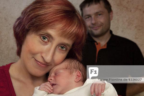 Porträt einer Familie  Mutter mit neugeborenem Jungen vorne  dahinter der Vater