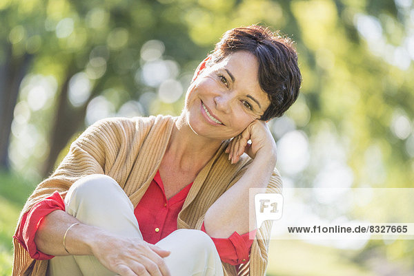 Mature woman sitting on grass in park