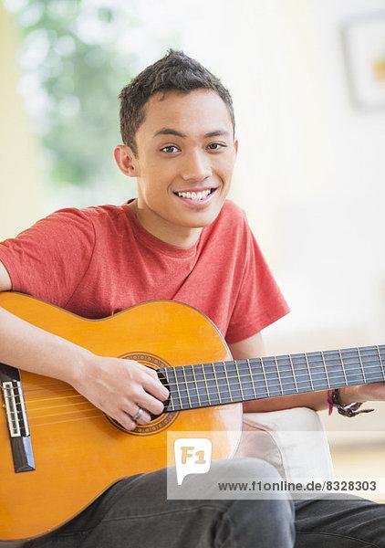 Junger Mann beim Gitarre spielen