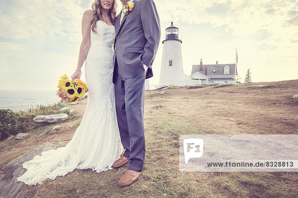 Low section of married couple  lighthouse in background