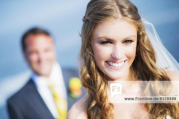 Portrait of smiling bride  groom in background