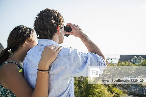 Rear view of couple  man looking through binoculars