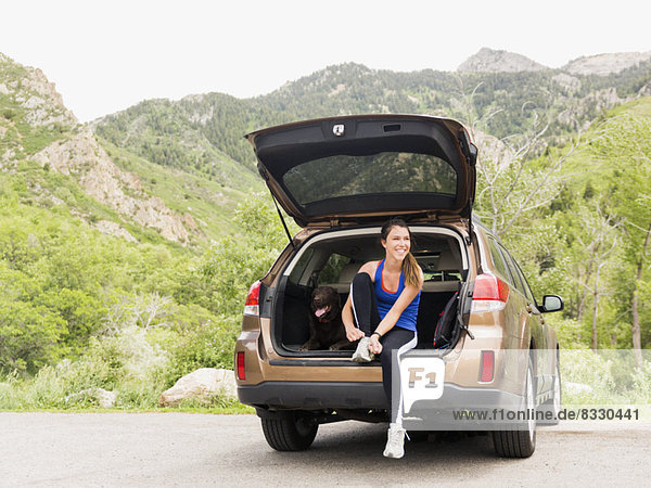 Woman wearing sportswear sitting at car trunk with dog