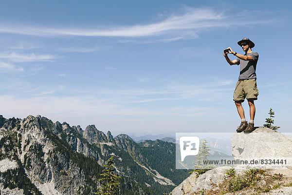 Ein Wanderer auf einem Berggipfel mit einem Smartphone in der Hand  auf dem Gipfel des Surprise Mountain  in der Alpine Lakes Wilderness  im Mount Baker-Snoqualmie National Forest.