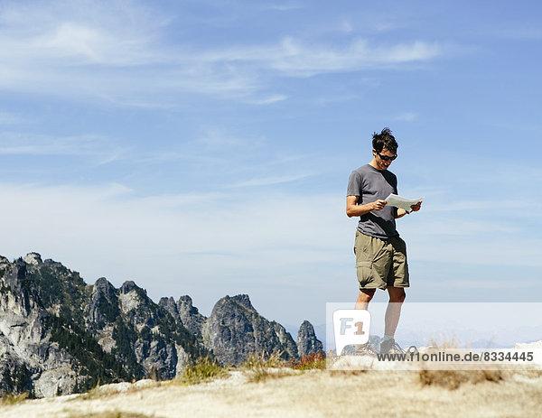 Ein Wanderer auf dem Berggipfel  der auf eine Karte schaut. Überraschungsberg  Alpine Lakes Wilderness  im Mount Baker-Snoqualmie National Forest