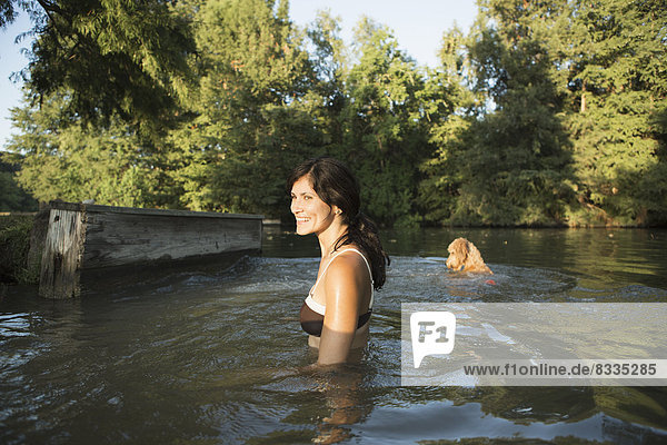 A woman swimming with her two dogs in a lake.