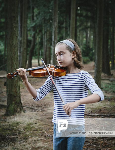 Ein zehnjähriges Mädchen spielt Geige im Discovery Park  Seattle.