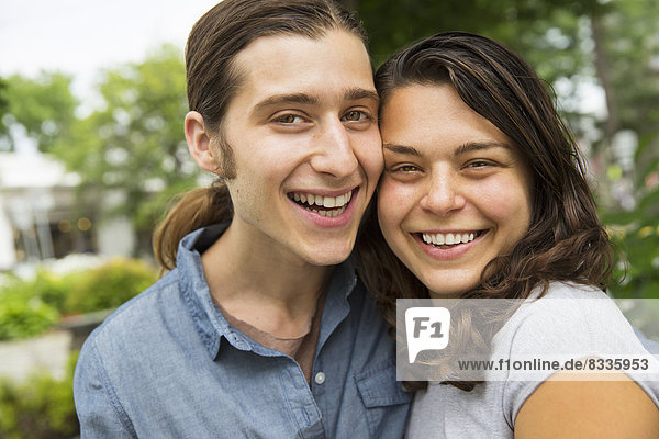 Ein junges Paar Seite an Seite  flirtet und fotografiert.