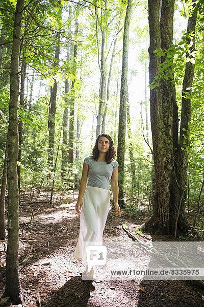Eine junge Frau auf einem Waldspaziergang.