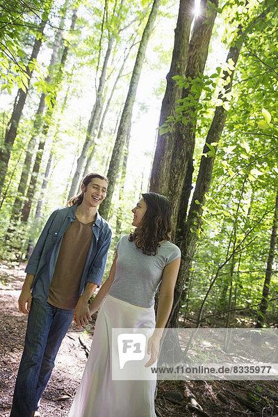 Zwei Menschen  eine junge Frau und ein Mann  gehen Seite an Seite im Wald spazieren.