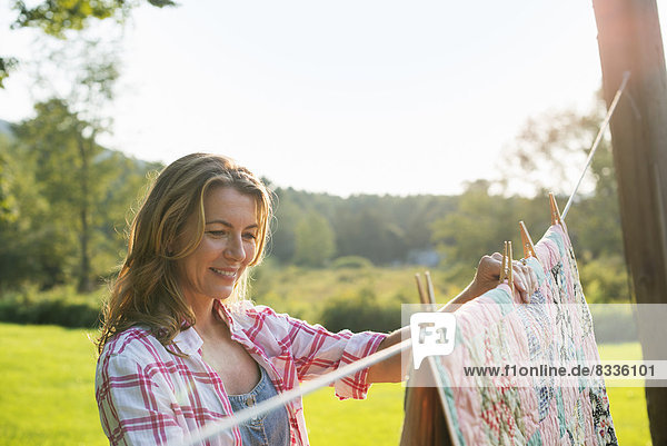 Eine Frau hängt Wäsche an der Wäscheleine  an der frischen Luft.