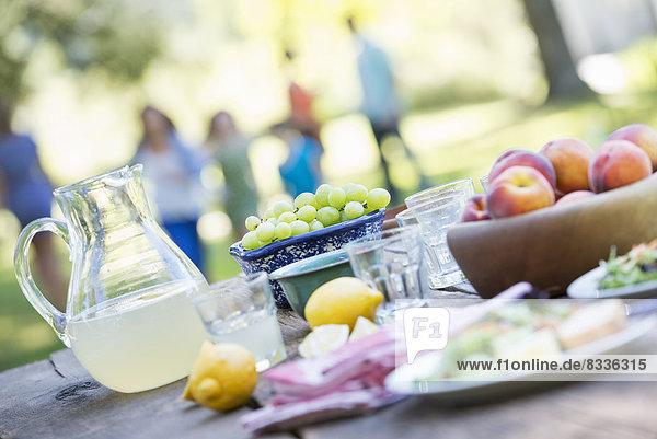 Ein sommerliches Buffet mit Obst und Gemüse  das auf einem Tisch aufgebaut ist. Menschen im Hintergrund.