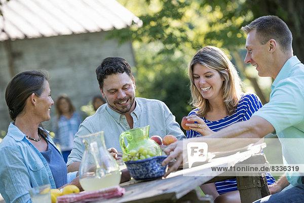 Eine Familie  Erwachsene und Kinder sitzen um einen Tisch herum und genießen gemeinsam eine Mahlzeit.