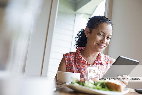 Eine junge Frau  die vom Bildschirm eines digitalen Tabletts liest  an einem Tisch sitzend. Kaffee und ein Sandwich.