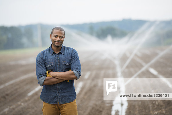 An organic vegetable farm  with water sprinklers irrigating the fields. A man in working clothes.