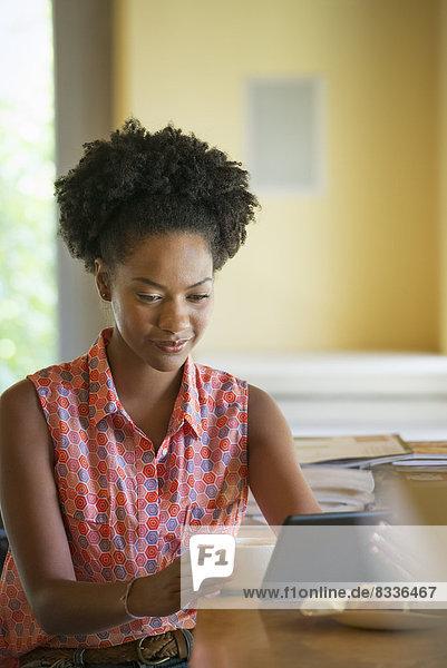 Eine Frau sitzt bei einer Tasse Kaffee. Sie hält ein eBook oder ein digitales Tablet in der Hand.