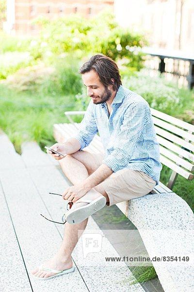 Vereinigte Staaten von Amerika  USA  benutzen  Mann  New York City  Telefon  Sitzbank  Bank  jung  Handy