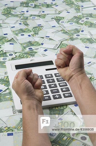 Mann macht Faust über Rechner auf 100-Euro-Banknoten