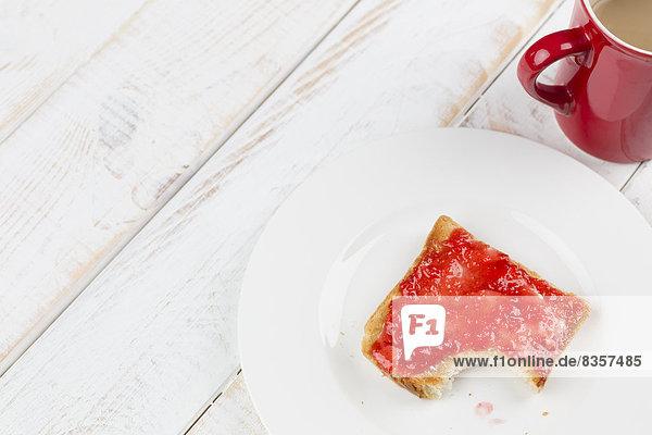 Gebissener Toast mit roter Marmelade auf Teller  Studioaufnahme