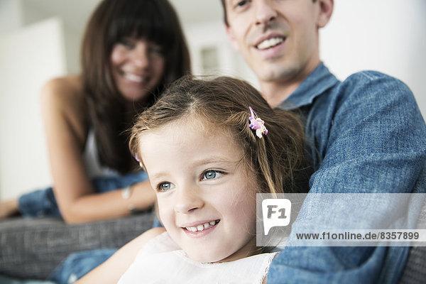 Junge Eltern mit kleiner Tochter  die zu Hause auf dem Sofa sitzt.