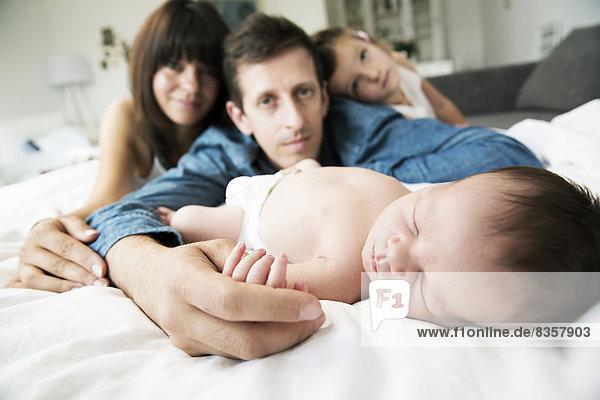 Junge Eltern mit kleiner Tochter und neugeborenem Sohn zu Hause