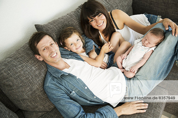 Junge Eltern mit männlichem Neugeborenen und kleiner Tochter  die zu Hause auf dem Sofa sitzt.