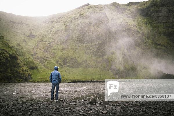 Iceland  Tourist at Skogafoss Waterfall