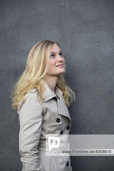 Blond woman in front of a wall
