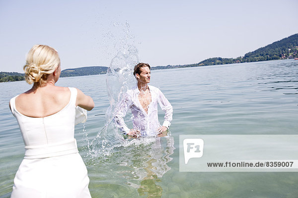 Germany  Bavaria  Tegernsee  Wedding couple standing in lake  pouring water over groom