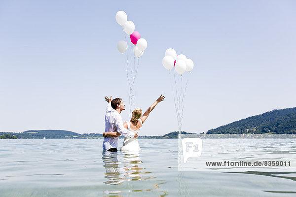 Deutschland  Bayern  Tegernsee  Hochzeitspaar im See stehend  Ballons haltend