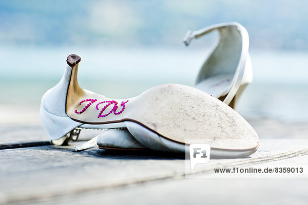 Germany  Bavaria  Tegernsee  Abandoned wedding shoes on jetty