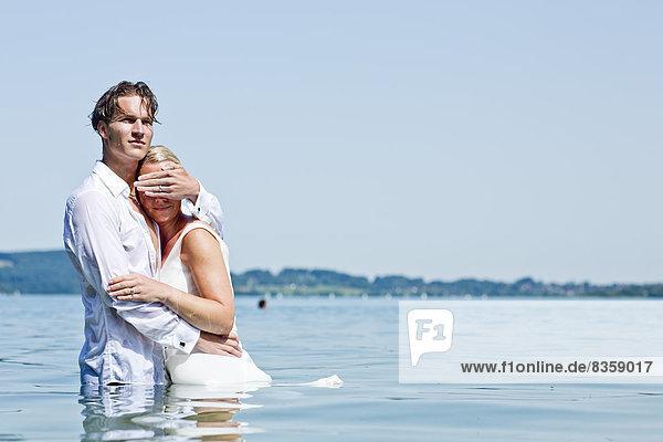 Hochzeitspaar steht im See  Mann schirmt Frauenaugen ab