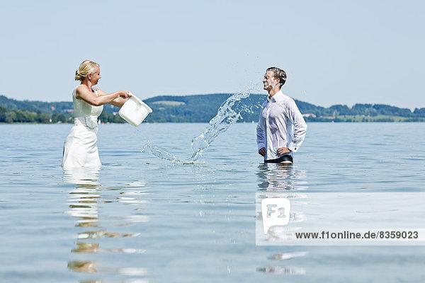 Deutschland  Bayern  Tegernsee  Hochzeitspaar im See stehend  Wasser über den Bräutigam gießend