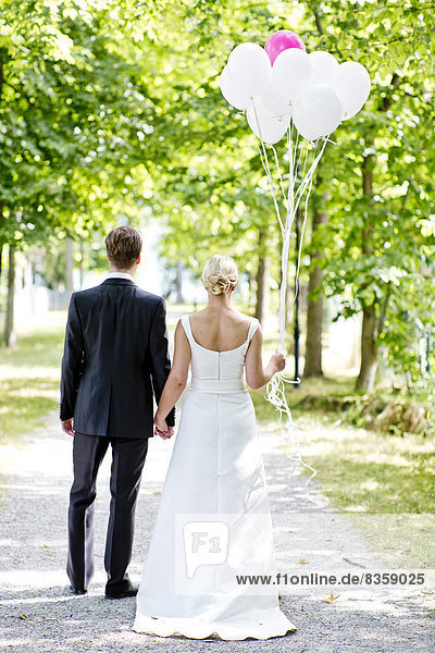Germany  Bavaria  Tegernsee  Wedding couple walking under trees  holding balloons