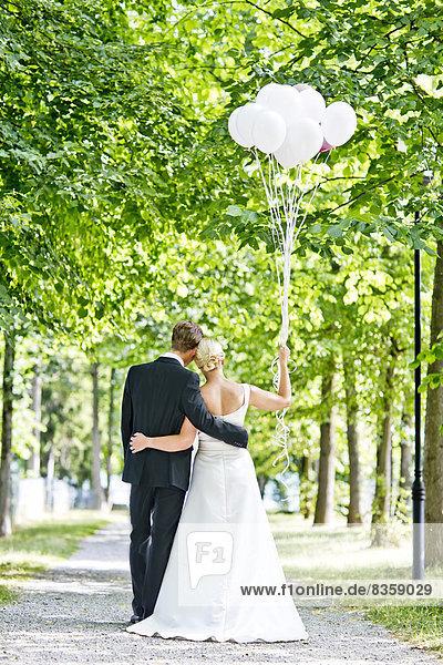 Deutschland  Bayern  Tegernsee  Hochzeitspaar unter Bäumen wandelnd  Ballon haltend