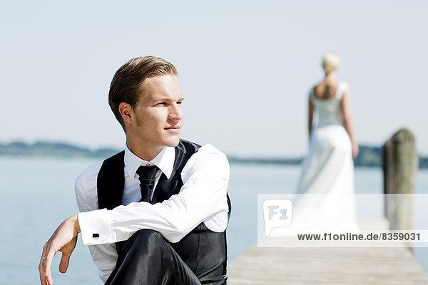 Germany  Bavaria  Tegernsee  Wedding couple on jetty