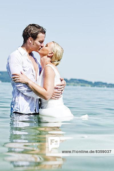 Deutschland  Bayern  Tegernsee  Hochzeitspaar im See stehend  küssend