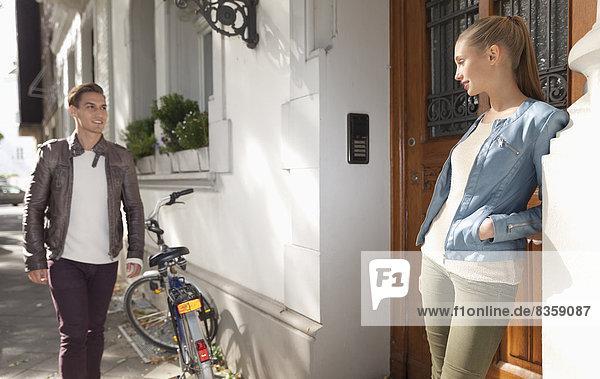 Junge Frau wartet auf ihren Freund vor einem Wohnhaus