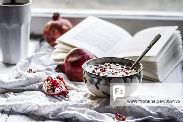 Healthy breakfast with pomegranate in yogurt  Coffee and opened book