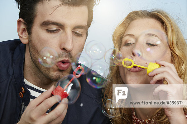 Germany  Dusseldorf  Young couple making soap bubbles