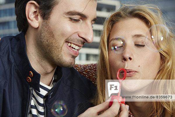 Deutschland  Düsseldorf  Junges Paar macht Seifenblasen