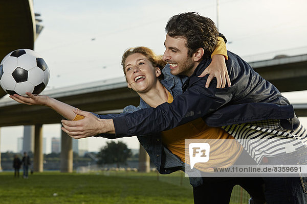 Germany  Dusseldorf  Young couple playing football