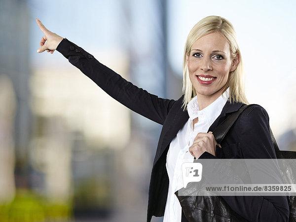 Porträt einer Geschäftsfrau  die auf etwas zeigt