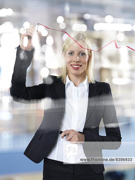 Porträt einer Geschäftsfrau mit roter Linie auf Glasscheibe