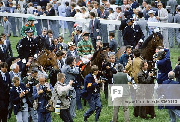 Press photographers and reporters surround the winning horse and jockey at Epsom Racecourse on Derby Day  UK